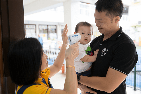 Madam Chan receiving the infants from parents in the mornings